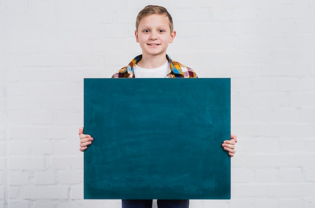 Retrato, de, um, menino, segurando, em branco, chalkboard, ficar, contra, branca, parede tijolo Foto gratuita
