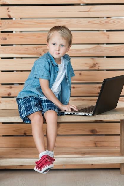 Retrato, de, um, menino sentando, ligado, banco, usando computador portátil Foto gratuita