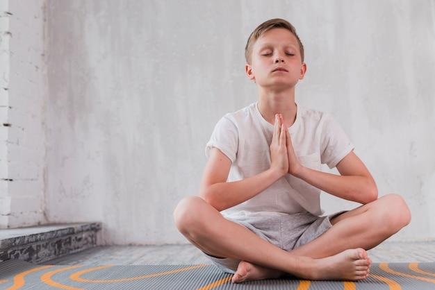 Retrato, de, um, menino sentando, ligado, esteira exercício, fazendo, meditação Foto gratuita