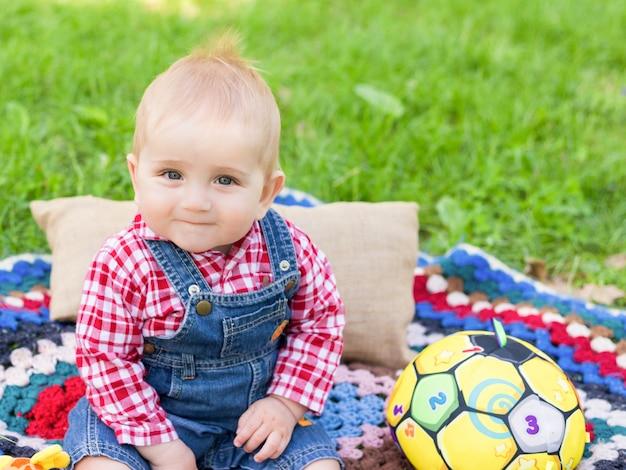 Retrato, de, um, menino sentando, ligado, um, cobertor, ligado, um, fresco, capim, em, um, parque cidade, em, verão Foto Premium
