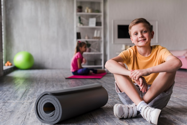 Retrato, de, um, menino sorridente, sentando, perto, a, enrolado, esteira exercício Foto gratuita