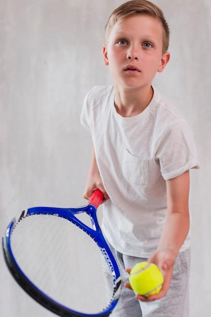 Retrato, de, um, menino, tocando, com, raquete, e, bola Foto gratuita
