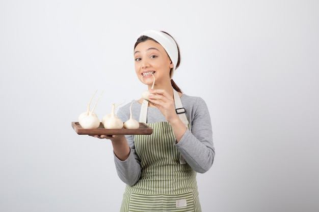 Retrato de um modelo de jovem segurando uma placa de madeira com rabanetes brancos. Foto gratuita