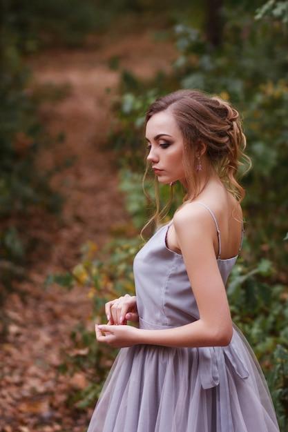 Retrato de um modelo de vestido roxo com um penteado bonito. fundo desfocado, efeito artístico. Foto Premium
