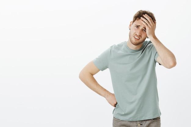 Retrato de um modelo masculino europeu sombrio e perturbado em roupa casual, segurando a palma da mão na testa e franzindo a testa, tocando o quadril com o braço, sentindo dor de cabeça por excesso de trabalho Foto gratuita
