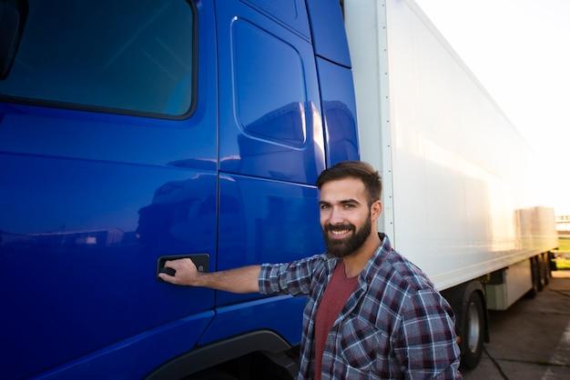 Retrato de um motorista de caminhão experiente parado por seu veículo longo semi-caminhão. Foto Premium