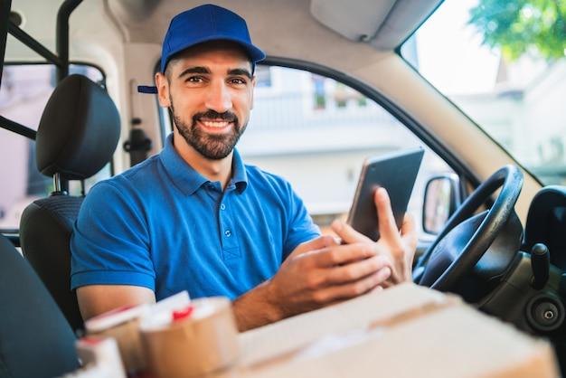 Retrato de um motorista de entregador usando tablet digital enquanto está sentado na van. serviço de entrega e conceito de transporte. Foto Premium