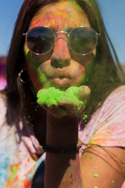 Retrato, de, um, mulher, desgastar, óculos de sol, soprando, verde, holi, pó Foto gratuita
