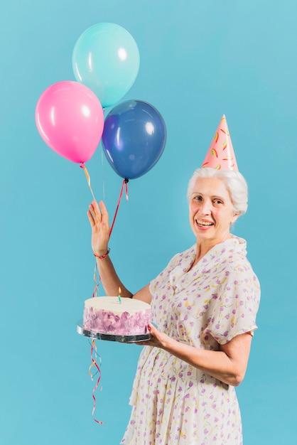 Retrato, de, um, mulher feliz, com, bolo aniversário, e, balões, ligado, azul, fundo Foto gratuita