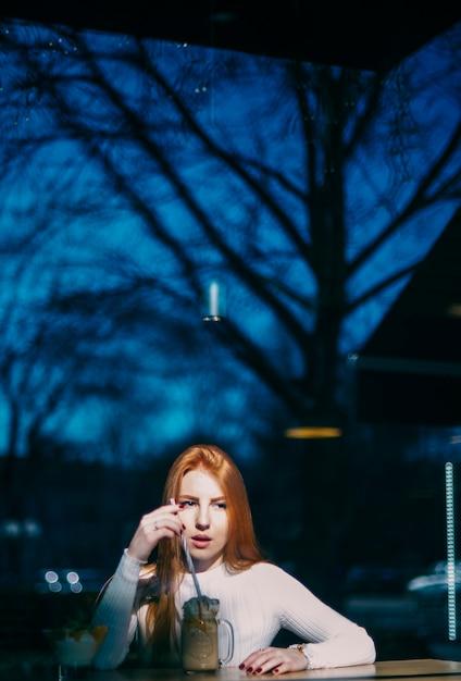 Retrato, de, um, mulher jovem, com, smoothie, jarro, em, caf� Foto gratuita