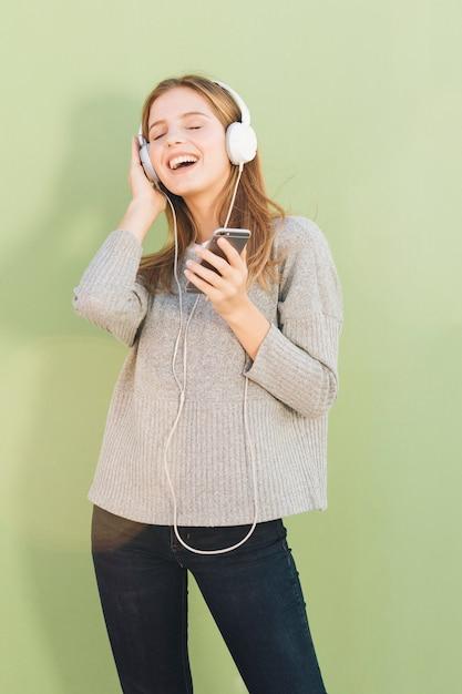 Retrato, de, um, mulher jovem, desfrutando, a, música, ligado, headphone, contra, hortelã, verde, fundo Foto gratuita