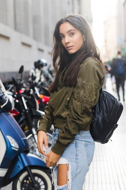 Retrato, de, um, mulher jovem, em, mochila preta, ficar, ligado, rua, olhando câmera Foto gratuita