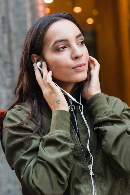 Retrato, de, um, mulher jovem, escutar música, ligado, fone ouvido Foto gratuita
