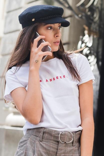 Retrato, de, um, mulher jovem, falando telefone móvel, com, forma coração, tatuagem, sobre, dela, mão Foto gratuita