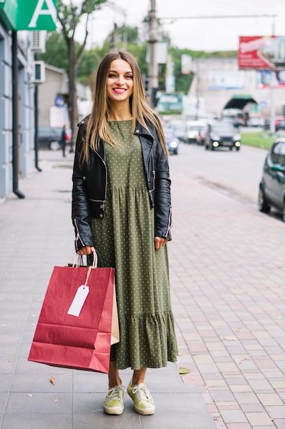 Retrato, de, um, mulher jovem, ficar, ligado, calçada, segurando, bolsas para compras, em, mão Foto gratuita