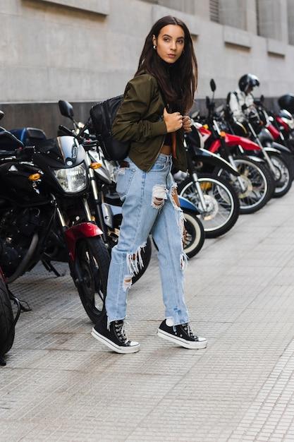 Retrato, de, um, mulher jovem, ficar, perto, a, estacionamento, bicicleta, ligado, calçada Foto gratuita