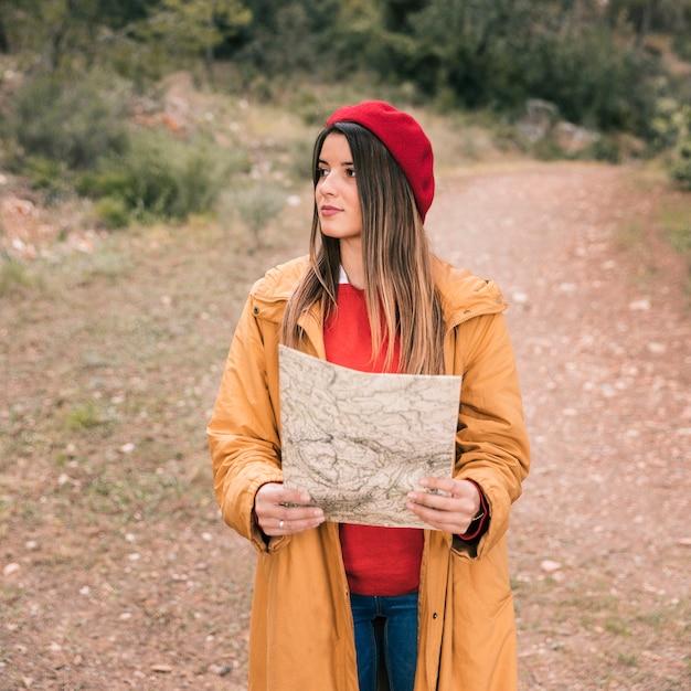 Retrato, de, um, mulher jovem, segurando, mapa, em, passe mão, ligado, rastro Foto gratuita