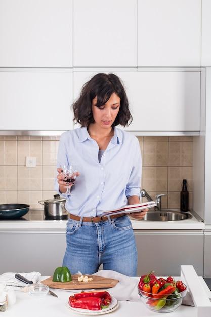 Retrato, de, um, mulher jovem, segurando, wineglass, em, mão, leitura, a, receita, após, preparar, a, alimento Foto gratuita