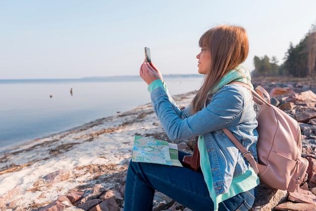 Retrato, de, um, mulher jovem, sentando praia, com, mapa, usando, telefone móvel Foto gratuita