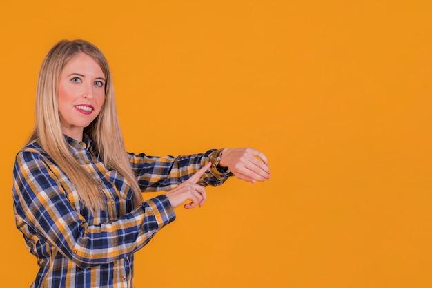 Retrato, de, um, mulher jovem, verificar, a, tempo, ligado, wristwatch, contra, um, fundo laranja Foto gratuita