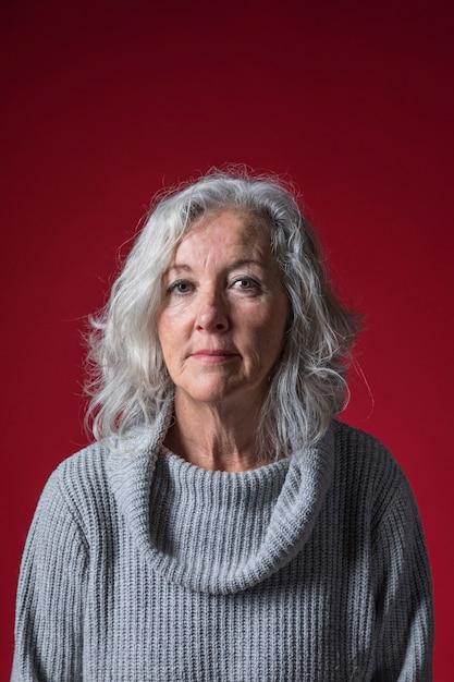 Retrato, de, um, mulher sênior, contra, vermelho, fundo Foto gratuita