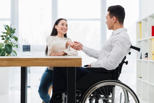 Retrato, de, um, mulher sorridente, apertando mão, com, incapacitado, homem jovem, sentando, ligado, cadeira roda Foto gratuita