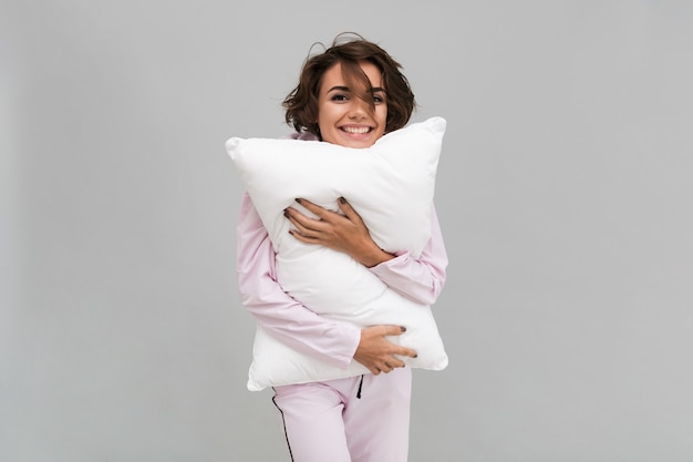 Retrato, de, um, mulher sorridente, pijama, segurando um travesseiro Foto gratuita