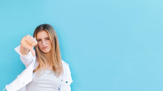 Retrato, de, um, nervoso, loiro, mulher jovem, mostrando, polegar baixo, contra, azul, fundo Foto gratuita
