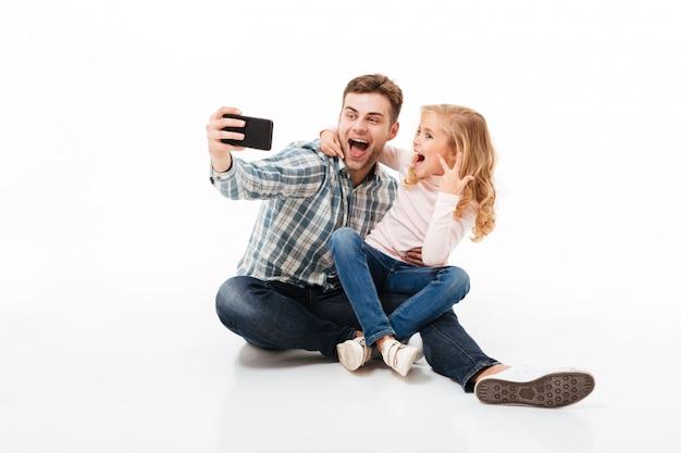 Retrato de um pai alegre e sua filha pequena Foto gratuita