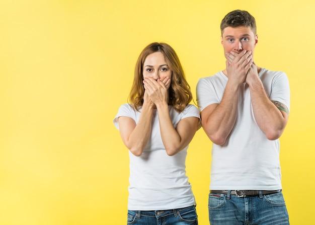 Retrato, de, um, par jovem, cobertura, seu, boca, contra, fundo amarelo Foto gratuita