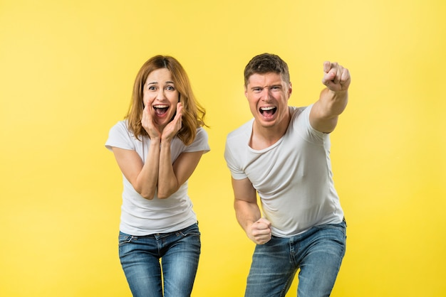 Retrato, de, um, par jovem, gritando, e, alegrando, com, alegria, contra, amarela, fundo Foto gratuita