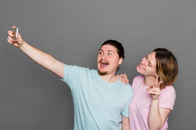 Retrato, de, um, par jovem, levando, selfie, ligado, esperto, telefone, contra, parede cinza Foto gratuita