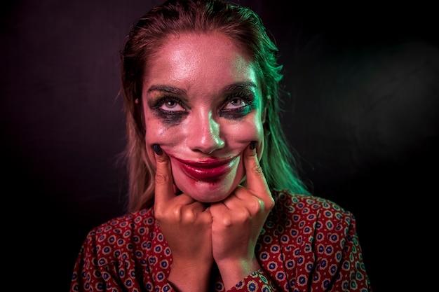 Retrato de um personagem de horror maquiagem palhaço sorrindo Foto gratuita