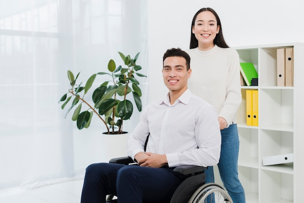Retrato, de, um, posição mulher, atrás de, a, sorrindo, homem negócios, sentando, ligado, cadeira rodas Foto gratuita