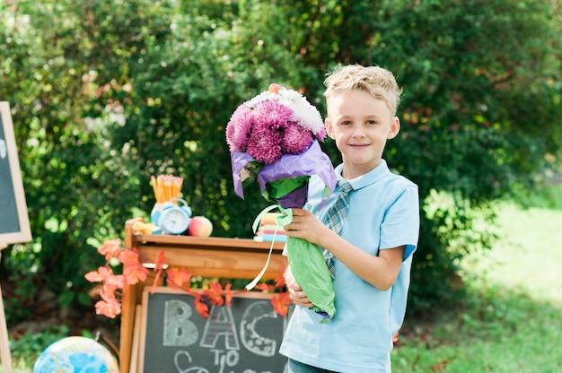 Retrato de um primeiro-graduador novo bonito com ramalhete em uma farda da escola no parque do outono do fundo. Foto Premium