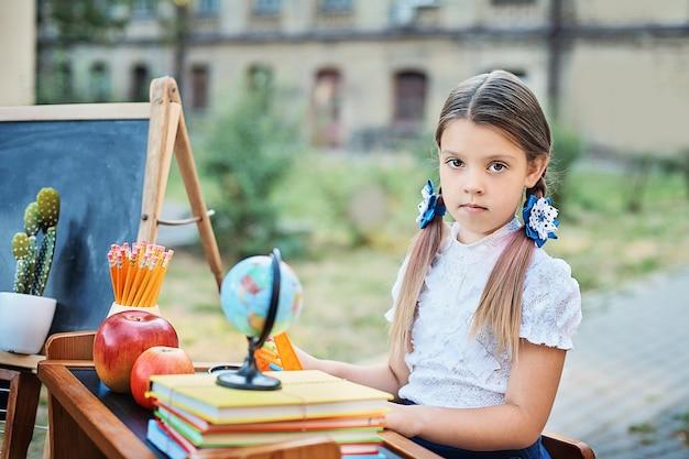 Retrato de um primeiro-graduador novo bonito que senta-se em uma mesa no parque do outono do fundo. Foto Premium