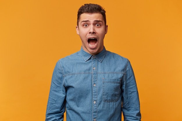 Retrato de um rapaz que grita em pânico, berra de medo, dá um grito alto porque está pasmo e muito assustado Foto gratuita