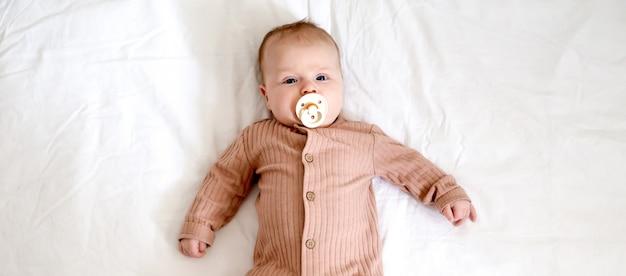 Retrato, de, um, recem nascido, menina bebê, mentindo, cama, com, um, mamilo, chupeta Foto Premium