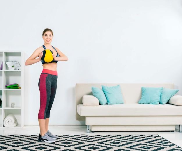 Retrato, de, um, saudável, mulher jovem, segurando, bola médica, em, mão Foto gratuita