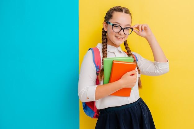 Retrato, de, um, schoolgirl, em, óculos, com, livros, livros texto, ligado, amarela azul Foto Premium