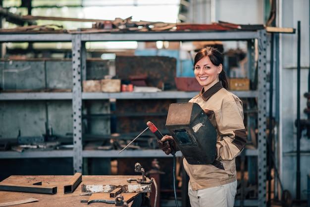 Retrato de um soldador fêmea bonito na fábrica da indústria pesada. Foto Premium