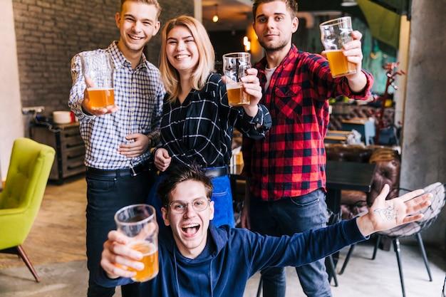 Retrato de um sorridente amigos segurando os copos de cerveja na mão comemorando Foto gratuita
