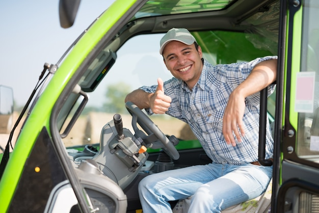Retrato, de, um, sorrindo, agricultor, dar, polegares cima, em, seu, trator Foto Premium