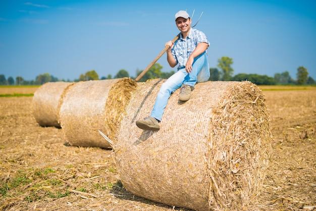 Retrato, de, um, sorrindo, agricultor, sentando, ligado, um, feno, pacote, em, seu, campo Foto Premium