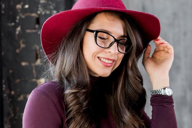Retrato, de, um, sorrindo, bonito, mulher jovem, com, chapéu cor-de-rosa, e, óculos pretos Foto gratuita