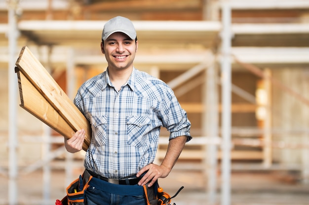 Retrato, de, um, sorrindo, carpinteiro, segurando, madeira, pranchas, em, um, local construção Foto Premium