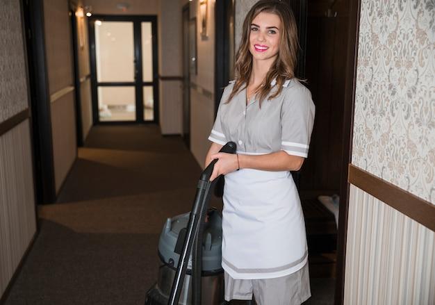 Retrato, de, um, sorrindo, chambermaid, ficar, em, a, hotel, corredor, segurando, aspirador de pó Foto gratuita