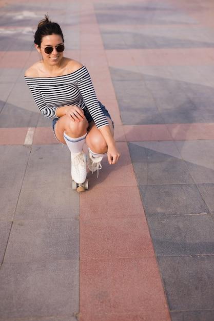 Retrato, de, um, sorrindo, elegante, jovem, mulher, crouching, chão Foto gratuita