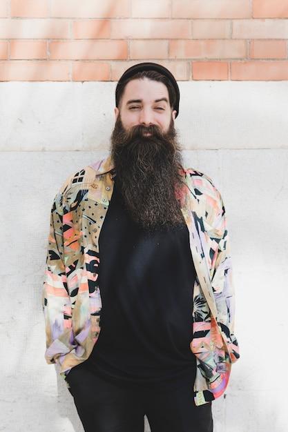 Retrato, de, um, sorrindo, homem barbudo, contra, parede tijolo Foto gratuita