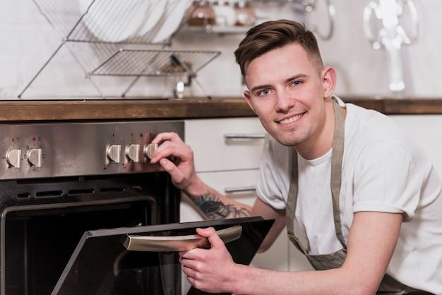 Retrato, de, um, sorrindo, homem jovem, abertura, a, forno, cozinha Foto gratuita